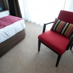 chambre avec fauteuil rembourré et coussins et rideaux